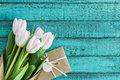 Light pink tulips bouquet and envelope on turquoise wooden tabletop with copy space