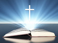 Light radiates from bible with cross under Royalty Free Stock Image