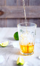 Light rum that pour in glass with ice limes around it proccess of making cuba libre cocktail or cola on wooden background Royalty Free Stock Photography