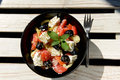 Light salad with vegetables and feta cheese healthy low calorie greek mixed in black bowl on white wooden table Stock Photo