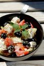 Light salad with vegetables and feta cheese healthy low calorie mixed in black bowl on white wooden table Royalty Free Stock Photos