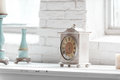 Light shabby chic interior fragment with clock and candlesticks