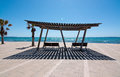 Light and shade seating benches with ocean view wooden structure mallorca balearic islands spain Royalty Free Stock Image