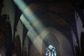 Light shafts stream into church window seeing the of sunshine through stained glass historic Royalty Free Stock Photo