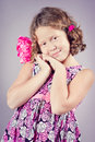 A light studio portrait of a beautiful girl in a pink dress and with a pink flower in her hair Stock Photos