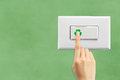 Light switch on a green wall background and hand ecology concept Stock Photography