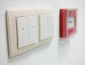 Light switch white with fire alarm button on the wall Stock Photography