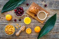Light tasty breakfast. Muesli, oranges, cherry, french croissant and milky coffee on wooden table background top view