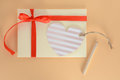 Light yellow envelope with a red ribbon, heart card and pencil on an apricot background Royalty Free Stock Photo