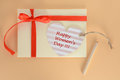 Light yellow envelope with a red ribbon and heart Happy Women Day card on an apricot background Royalty Free Stock Photo