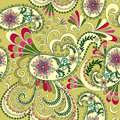 Light yellow paisley decorated with leaves and fl flowers on a green background Stock Photo