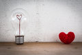 Lightbulb with heart shaped filament and red heart shaped silk on wood floor white background Stock Photos