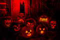 Lighted halloween pumpkins with candles group of candle lit carved in scarey lighting skull in background Royalty Free Stock Photo