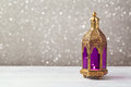 Lightened lantern on wooden table over bokeh background. Ramadan kareem holiday celebration
