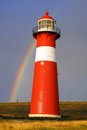 Lighthouse on background of the Rainbow. Royalty Free Stock Image
