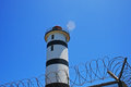 LIGHTHOUSE BEHIND SECURE FENCE Royalty Free Stock Photo