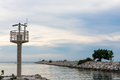 Lighthouse and cement seawall in evening landscape view Stock Image