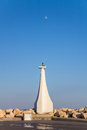 Lighthouse At The Entrance To The Marina On A Background Of Blue Sky With The Moon Royalty Free Stock Photo
