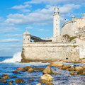 The lighthouse and fortress of el morro in havana with waves beaking against wall Royalty Free Stock Photography