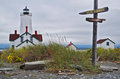 Lighthouse with fun signs serenity and reality at dungeness spit near sequim washington state the on the post say welcome to miles Royalty Free Stock Images