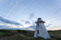 Lighthouse with jet trails an almost fallen down sits while or chemical pass by from a large plane Royalty Free Stock Photo