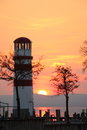 Lighthouse on a lake at sundown scenic view of silhouetted the shoreline of wide Stock Photos