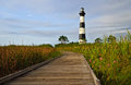 Lighthouse in the morning sun a well worn boardwalk provides a trail through marshland surrounding bodie island outer banks of Royalty Free Stock Photography