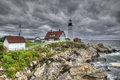Lighthouse by ocean on rocks a and its surrounds buildings sit top of the Royalty Free Stock Photography