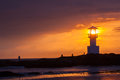Lighthouse s searchlight beam through marine at sunset Stock Photos