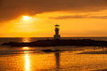 Lighthouse searchlight beam through marine at sunset Royalty Free Stock Image