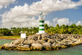Lighthouse on stones near water and palm trees Royalty Free Stock Photo