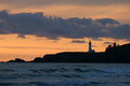 Lighthouse at sunset on the pacific ocean a distant a dark jetty cliff is sihouetted by a a in america Stock Images