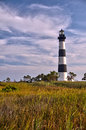 Lighthouse surrounded by clouds and marshland framed against a cloudy sky surrounds the bodie island in the outer banks of north Stock Images