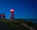 Lighthouse at twilight a light house with it s light on next to an open body of water Royalty Free Stock Photos