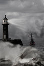 Lighthouse under the storm a tower projects its light through as a sailboat tries to join coast Stock Images