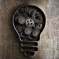 Lighting bulb business concept with working gears and cogs in rusty metal background Royalty Free Stock Image