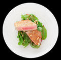 Lightly seared tuna steak isolated with sesame and fresh salad on black Royalty Free Stock Photo