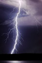 Lightning bolt large bright strikes from the storm clouds above Royalty Free Stock Image