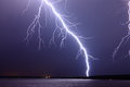 Lightning bolt at night very close and intense strikes near a shoreline on a lake Royalty Free Stock Images