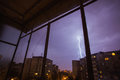 Lightning bolt real in city during a storm seen from house window Royalty Free Stock Image
