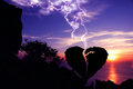 Lightning down to the broken heart-shaped stone,Silhouette Valentine background co Royalty Free Stock Photo