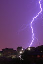 Lightning flash a thunderbolt hits the hill of a residential area coloring the night sky into purple Stock Images