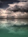 Lightning storm reflected onto a calm sea in the distance upon an otherwise ocean with sandy bottom Royalty Free Stock Image