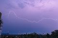 Lightning strike over city sky at twilight Royalty Free Stock Photos