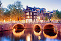 Lights of amsterdam canal bridges illuminated at evening netherlands north holland province Royalty Free Stock Photo