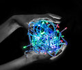 Lights in the hands of holding a bowl multi colored electric light bulbs Stock Images