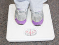 Lightweight child on bathroom scales a young wearing silver and purple sneakers stands white Stock Photo