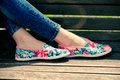 Lightweight summer shoes girl feet in on wooden bench Royalty Free Stock Images