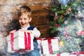 Liitle boy opening gift box little under christmas tree in wooden house interior Stock Photo
