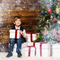 Liitle boy opening gift box little under christmas tree in wooden house interior Royalty Free Stock Photo
